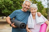 Lovely senior man and old woman holding yoga mat for exercising outdoor. Aged husband and wife ready poster