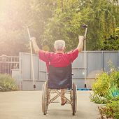 Back View Of An Older, Handicapped Man, Arms And Crutches Raised In Happiness, Sunflare poster