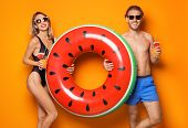 Happy Young Couple In Beachwear With Inflatable Ring And Cocktails On Color Background poster