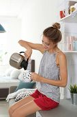 Beautiful Young Woman Pouring Tea Into Cup In Kitchen At Home. Lazy Morning poster