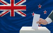 Man Voting On Elections In New Zealand In Front Of Flag