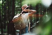 Back View On Traveler Backpack And Hipster Girl Wearing Hat. Young Brave Woman Traveling Alone Among poster