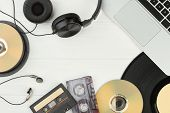 Table With Audio Music Technologies. Frame From Laptop, Vinyl Record, Earphones, Compact Discs And A poster