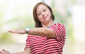 Young adult woman with down syndrome over isolated background gesturing with hands showing big and l poster