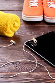 Sport Shoes, Towel, Earphones And Tablet. Sneakers, Computer Tablet, Earphones And Towel On Wooden S poster