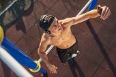 Top View Image Of Athletic Smilnig Young Male Relaxing After Training On Workout Ground Outdoors Mak poster