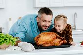 Happy Father And Daughter Sniffing Freshly Baked Thanksgiving Turkey poster