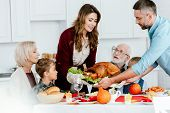 Happy Adult Couple Carrying Baked Turkey For Thanksgiving Dinner With Big Family At Home poster