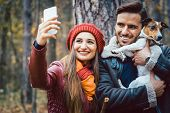 Woman and man with their dog on autumn walk taking a phone selfie posting it online on social media poster