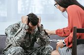 Female Psychiatrist Supporting Soldier With Post Traumatic Syndrome During Therapy Session poster