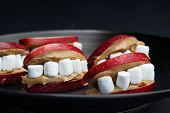 Fun Food For Kids. Halloween Apple Mouths Filled With Peanut Butter With Mini Marshmallows For Teeth poster