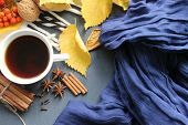 A Cup Of Hot Tea Yellow Autumn Leaf And Spices, Cinnamon Sticks, Anise, Cloves On A Blue Scarf Backg poster
