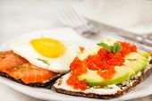 Avocado And Red Caviar, Smoked Salmon And Fried Egg Rye Toasts For Breakfast, Close Up poster