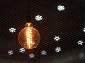 Tungsten Orange Light Bulb Hanging On The Inside Of The Building With A Black Iron Fence Around. poster