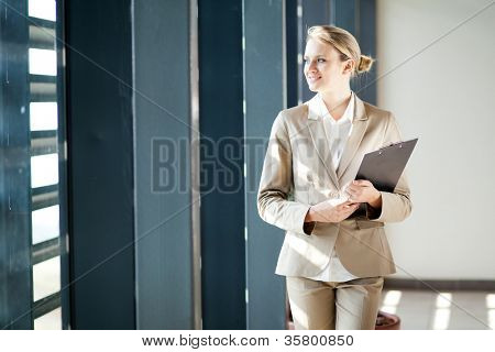 beautiful young businesswoman looking outside office window