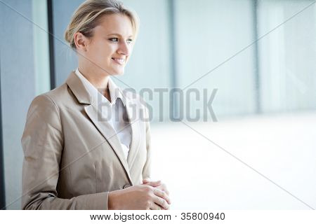 pretty businesswoman standing by office window