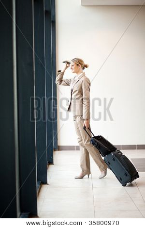 young businesswoman looking outside airport window