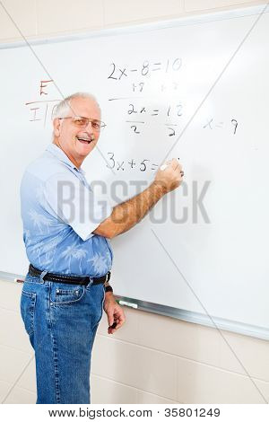 Middle aged teacher or adult education student writing algebra equations on the board.
