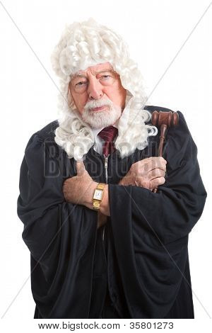 British judge in a wig, with his arms crossed looking stern, serious, and angry.  Isolated on white.