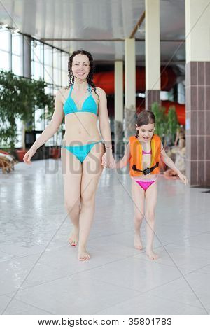 Happy wet mother and little daughter walk after swimming in pool.