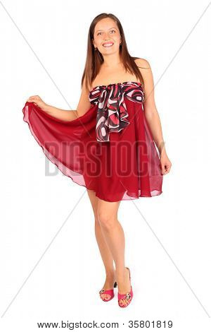 Beautiful young woman dressed in red pareo poses in studio on white background.