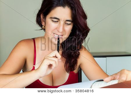 Adult hispanic woman reading a book and biting a pen while she studies
