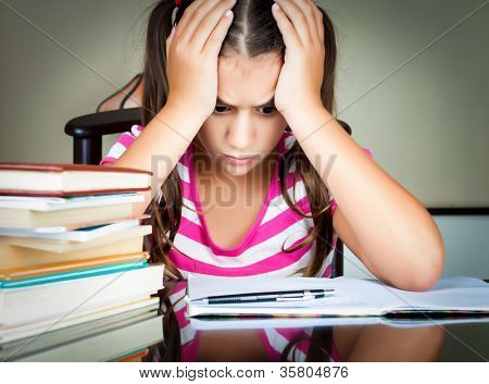 Angry and tired schoolgirl studying with a pile of books on her desk