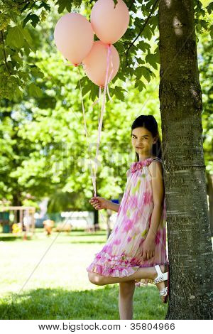 Cute little girl with pink balllons, standing outdoors