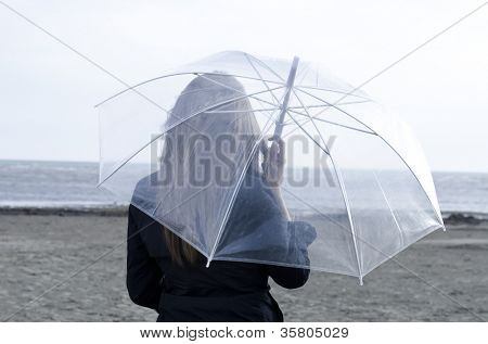 Young woman enjoying a rainy and windy day on the beach