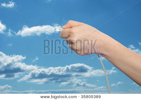 Concept or conceptual human or man hand holding internet data cable in clouds over the blue sky, as a metaphor for plug, connection, technology, share, network, mobility, connectivity or communication