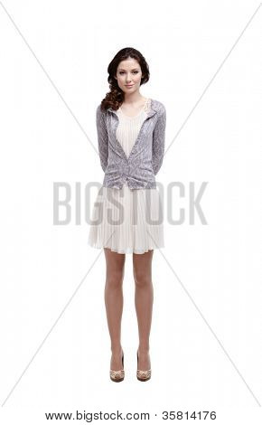 Confused young woman keeps her hands over the back, isolated on white