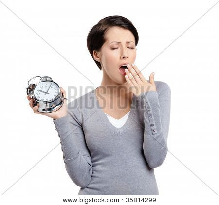 Yawning pretty woman holds an alarm clock, isolated on white