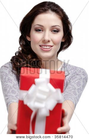 Young woman gives a gift wrapped in red paper, isolated on white