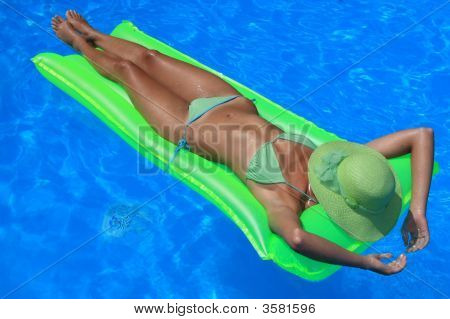 Woman Lying On An Air Matress In Blue Pool
