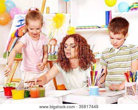 Child with female teacher painting  in start school.