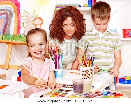 Child with teacher painting  in start school.
