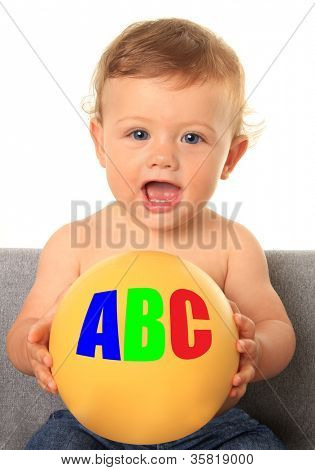 Adorable ten month old baby boy holding a yellow ball with ABC's.  Also available without text, add your own.