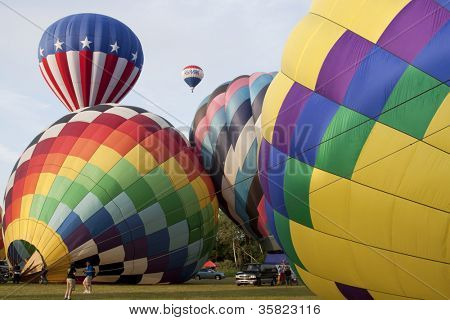 READINGTON, NJ-JUL 29: Hot air balloons on the field of the launch area preparing to ascend at the Quick Chek New Jersey Festival of Ballooning on the morning of July 29, 2012 in Readington, NJ.