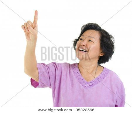 60s Asian senior woman pointing on transparent virtual screen button, over white background