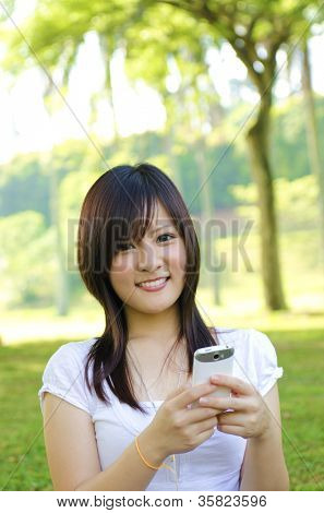 Happy oriental Asian young student using mobile phone to online / texting / sms , outdoor green park