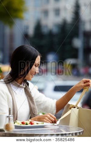 Image of happy female looking at paperbags in urban environment