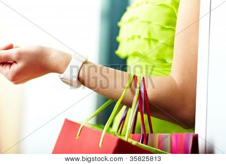 Image of shopaholic arm with three shopping bags