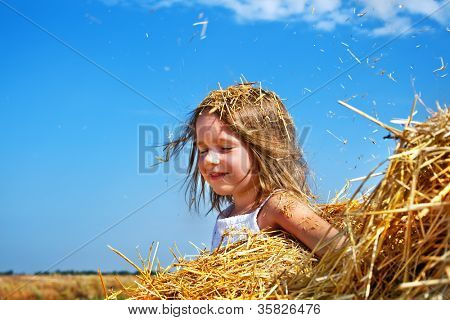 Portrait of a happy girl with closed eyes, sitting in a haystack
