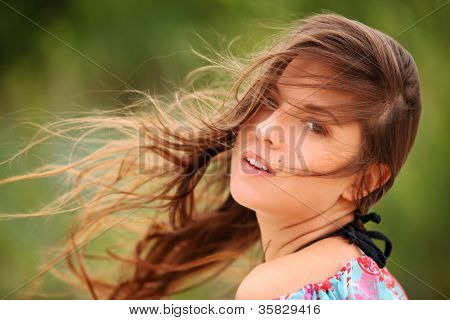 Portrait of  young woman smiling with windswept hair