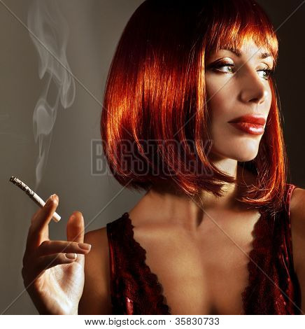 Luxury close up portrait of attractive girl, beautiful lady with fashionable red hairstyle smoke cigarette, young smoker woman relaxation indoor, cute female isolated on dark background