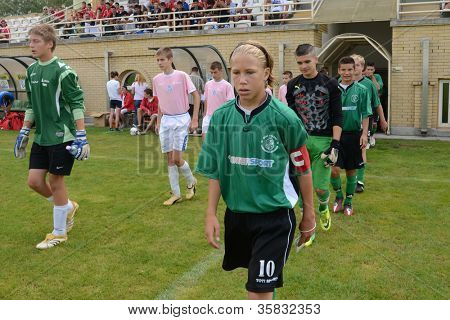 KAPOSVAR, HUNGARY - JULY 21: Unidentified competitors march in into the stadium at the VIII. Youth Football Festival U14 match Tirgu Mures (pink) (ROM) vs. Kaposvar (green)(HUN) on July 21, 2012 in Kaposvar, Hungary