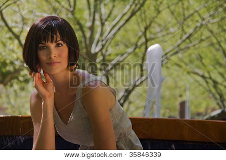 Attractive, Successful Young Woman Sitting Next To Fountain