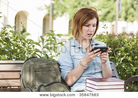 Stunned Young Pretty Female Student Outside with Backpack and Books Sitting on Bench Texting on Cell Phone.