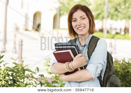 Smiling Young Pretty Female Student Standing Outside with Books and Backpack.