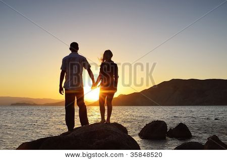 Girl and boy holding hands and watching the sun by the sea